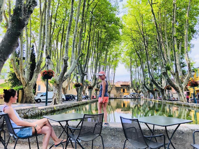 Frau in einem Café an einem Wasserbecken in Cuceron, Provence