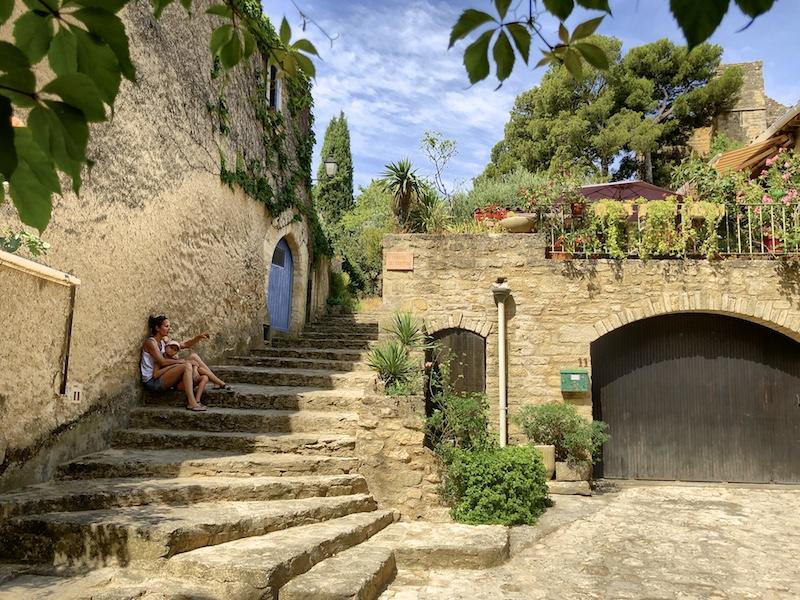 Frau mit Kind auf Treppe in Altstadt von Cuceron, Provence