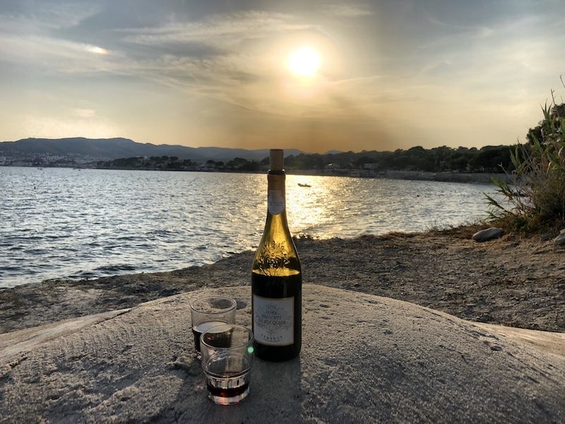 Flasche Rotwein und zwei Gläser auf mauer am Meer in La Ciotat, Cassis, Südfrankreich