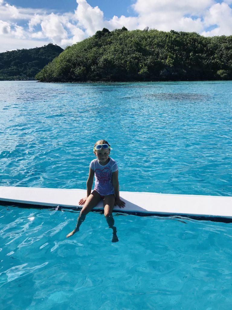 Kind auf einem Boot im Meer vor Bora Bora